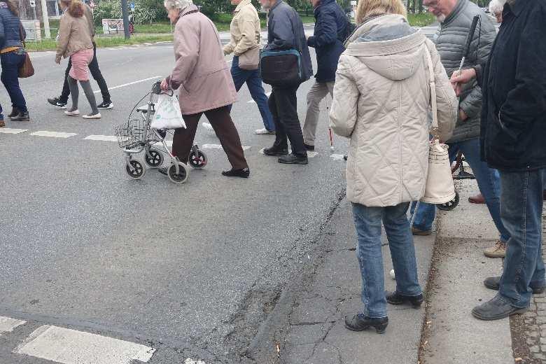 Passanten queren schlechte Straße